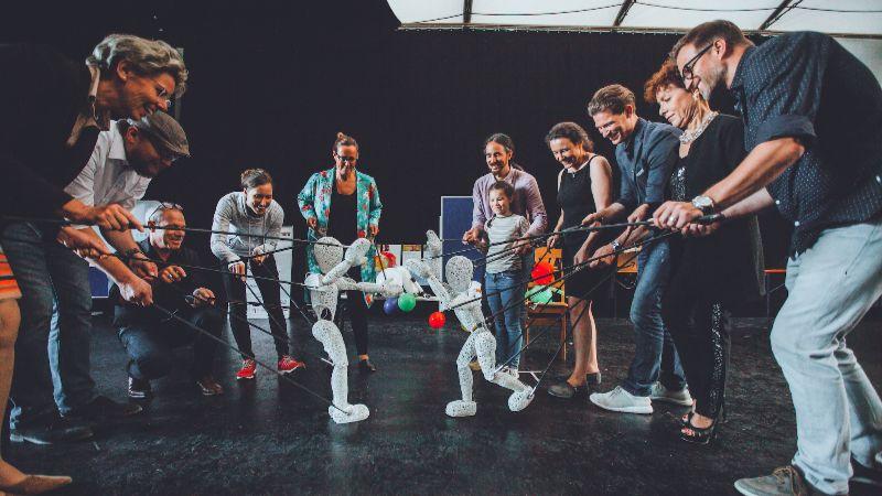 Menschen spielen ein Puppenspiel auf Bühne