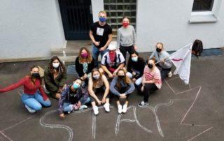 Praktikanten mit Masken vor dem Stay Büro